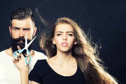 Closeup view of young beautiful couple of beautiful fashionable female barber cutting and holding scissors and handsome man with long beard in studio on black background, horizontal picture